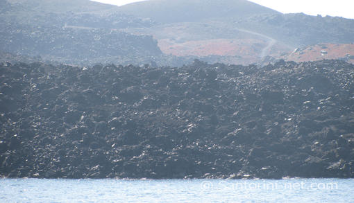 The black rocks of the volcano in Nea Kameni, falling to the Aegean sea